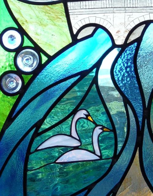 Stained glass swans on water